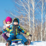 Two cute kids riding a sled and having fun